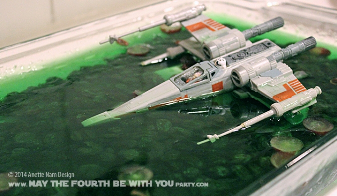 Star Wars Food: Dagobah Swamp Jell-o with crashed X-Wing /// Check out our blog for lots of Star Wars Party food recipes and downloadable labels! Great for a Birthday Party or a May the Fourth be with you Party. /// #starwars #starwarsparty #maythefourthbewithyou #starwarsbirthday #starwarsfood #luke #xwing #dagobah #jello maythefourthbewithyoupartyblog.com