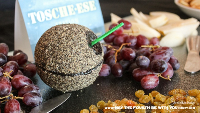 Star Wars Food: Pepper-encrusted Blue Cheese Death Star Cheese Ball with Grapes /// Check out our blog for lots of Star Wars Party food recipes and downloadable labels! Great for a Birthday Party or a May the Fourth be with you Party. /// #starwars #starwarsparty #maythefourthbewithyou #starwarsbirthday #starwarsfood #cheese #bluecheese maythefourthbewithyoupartyblog.com